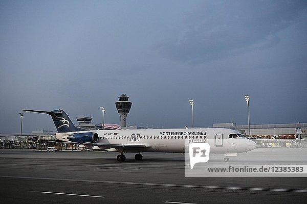 Montenegro Airlines  Fokker  F100  rollend vor Terminal 1 mit Tower  in der Dämmerung  Flughafen München  Oberbayern  Bayern  Deutschland  Europa