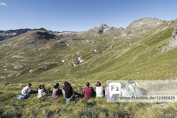 Children sitting in a mountain meadow  environmental education activities  Youth at the top event  Mont Avic Natural Park  Aosta Valley  Italy  Europe