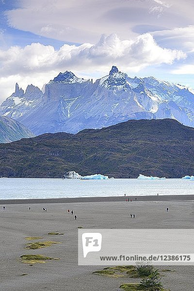 Tourists on the shore of Lake Grey with ice floes  Los Cuernos massif in the background  Torres del Paine National Park  Última Esperanza Province  Chile  South America
