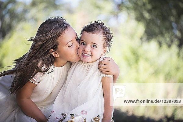 Siblings  big sister gives little sister a kiss