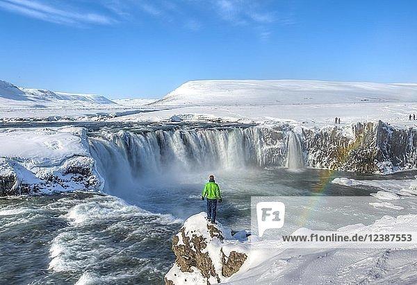 Junger Mann steht auf einem Felsen  Wasserfall mit Regenbogen  Góðafoss  Godafoss im Winter mit Schnee und Eis  Norðurland vestra  Nordisland  Island  Europa