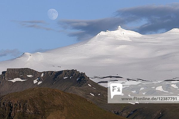 Snow-covered Snæfell volcano with Snæfellsjökul glacier and full moon  volcanic landscape near Hellissandur  Snæfellsnes peninsula  western Iceland