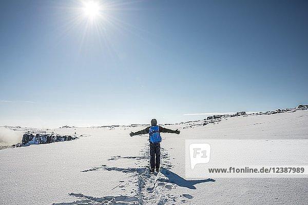 Junger Mann läuft durch verschneite Landschaft  Wanderweg zum Dettifoss  Norðurland eystra  Island  Europa