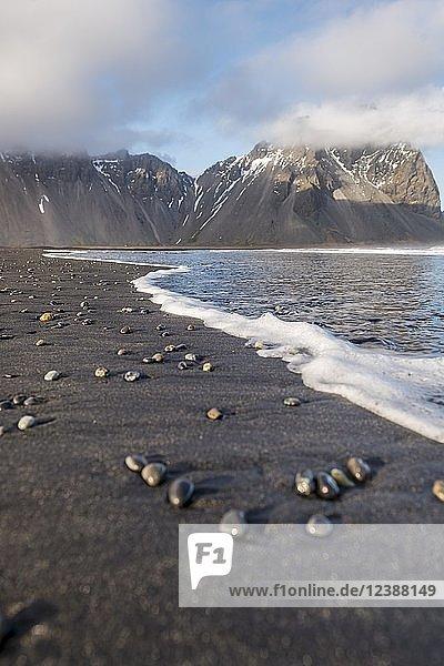 Steine an schwarzem Sandstrand  Berge Klifatindur  Eystrahorn und Kambhorn  Landzunge Stokksnes  Bergmassiv Klifatindur  Austurland  Ostisland  Island  Europa