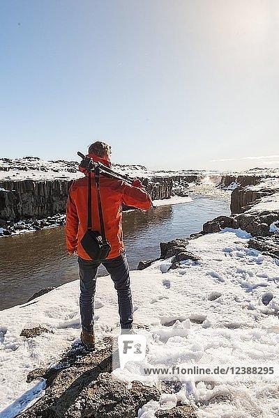 Mann mit Kamera-Ausrüstung blickt auf Selfoss Wasserfall im Winter  Schlucht  Nordisland  Island  Europa