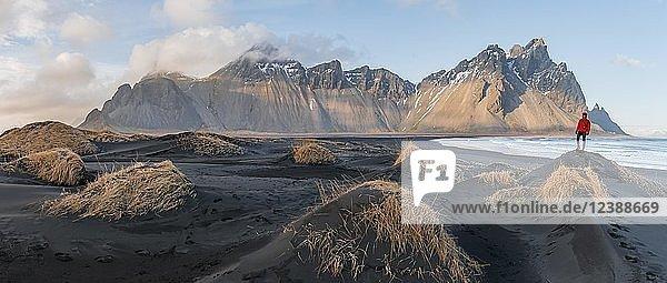 Mann mit roter Jacke steht auf Dünen mit trockenem Gras  schwarzer Lavastrand  Sandstrand  Berge Klifatindur  Eystrahorn und Kambhorn  Landzunge Stokksnes  Bergmassiv Klifatindur  Austurland  Ostisland  Island  Europa