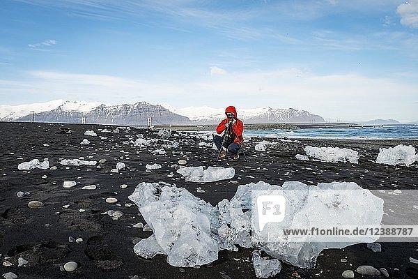 Tourist fotografiert Eisschollen an schwarzem Lavastrand  Diamond Beach  Fjallsárlón Gletscher Lagune  Ostisland  Island  Europa