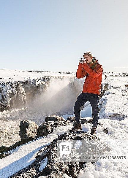 Fotografierender Mann am Selfoss Wasserfall im Winter  Schlucht  Nordisland  Island  Europa