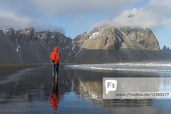 Mann  Tourist läuft an schwarzem Sandstrand  Lavastrand  Spiegelung  Berge Klifatindur  Eystrahorn und Kambhorn  Landzunge Stokksnes  Bergmassiv Klifatindur  Austurland  Ostisland  Island  Europa