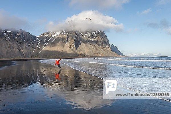 Mann rennt gut gelaunt an schwarzem Sandstrand  Berge Klifatindur  Eystrahorn und Kambhorn  Landzunge Stokksnes  Bergmassiv Klifatindur  Austurland  Ostisland  Island  Europa