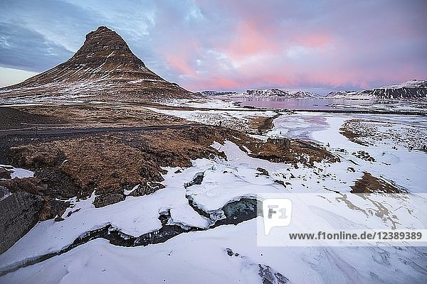 Kirkjufell mountain  Kirkjufellfoss waterfall frozen up in front  cloudy sky with sunset  Grundarfjördur fjord  western Iceland  Iceland  Europe