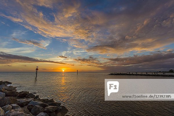 Colorful sunset over the Gulf of Mexico and the Gulf Intracoastal Waterway at the Venice Jetty in Venice Florida.