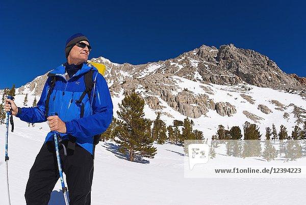 Backcountry skier climbing Piute Pass  John Muir Wilderness  Sierra Nevada Mountains  California USA.