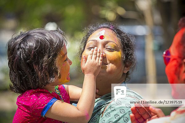 A child is staging his mother Abir's color at the time of Holi in Dhaka  Bangladesh.