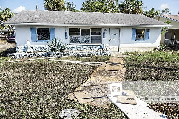 Florida  Bonita Springs  after Hurricane Irma damage destruction aftermath    flooding  house  home  muddfy yard  plywood pathway  exterior  flood depth water line
