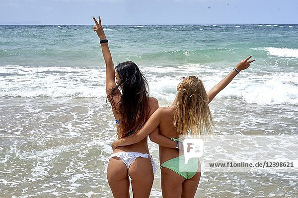 Rear view of two young women at beach in bikini. Malia  Crete  Greece.