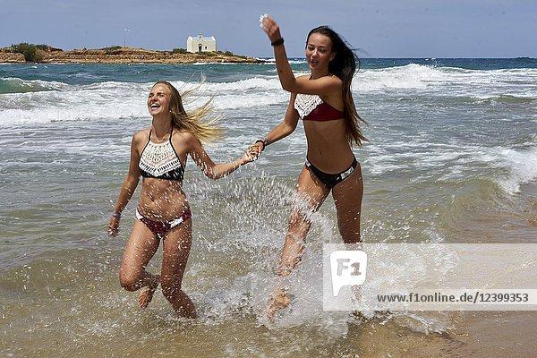 Two women running at beach in sea water  wearing bikini. Having fun. Holiday location Greece  Crete  Malia