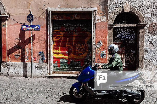 Man riding a bicycle on the streets of Trastevere neighbourhood  Rome  Lazio region  Italy.