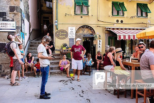 Tourists reliefing from summer heat in a typical bar terrace  Vernazza  Cinque Terre  Liguria  Italy.
