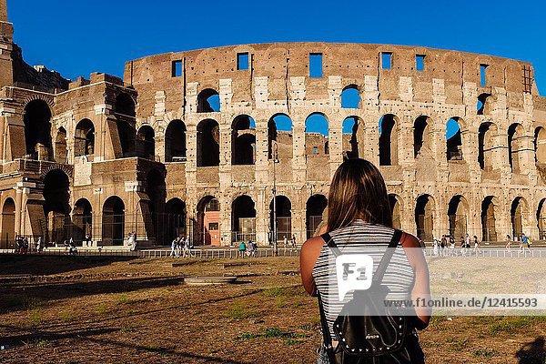 Tourist photographing the Colosseum amphitheatre,  Rome,  Lazio region,  Italy.