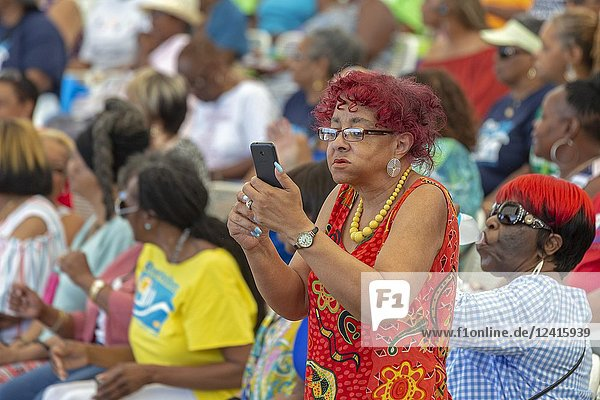 Detroit  Michigan - A woman uses her cell phone to film the action during Senior Friendship Day  an event that brought several thousand senior citizens to Chene Park for music  dancing  and food. The event was sponsored by the City of Detroit and the Detroit Area Agency on Aging.