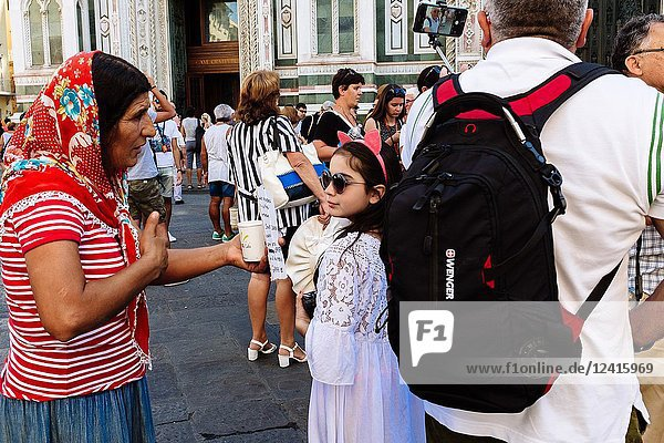 Old woman begging tourists outside Florence Cathedral in Piazza del Duomo  Florence  Tuscany  Italy.