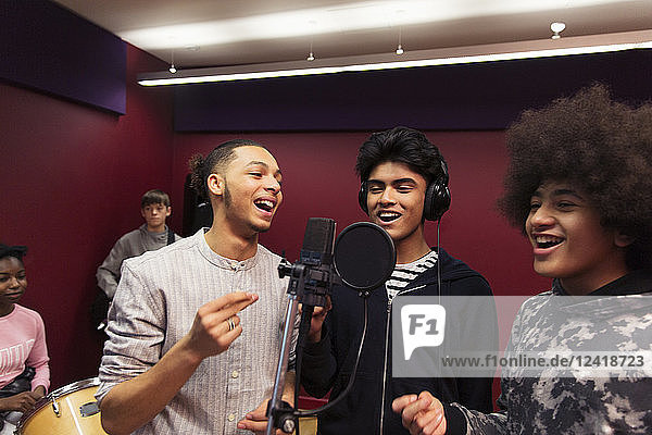 Smiling teenage boy musicians recording music  singing in sound booth