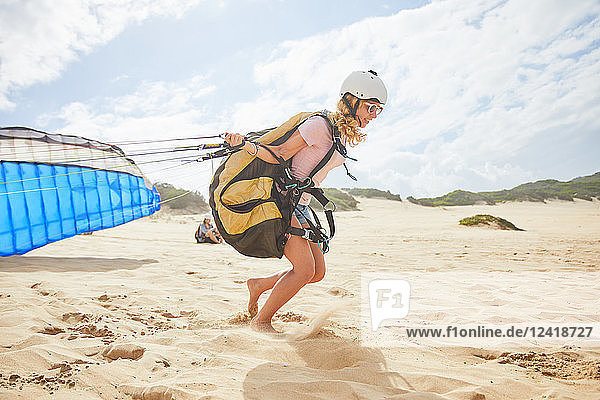 Female paraglider running with parachute on sunny beach