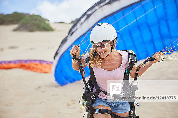 Smiling female paraglider with parachute on beach