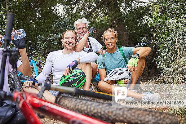 Portrait smiling male friends mountain biking  resting in woods