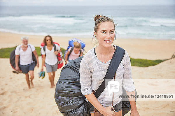 Portrait smiling  confident female paraglider carrying parachute backpack on beach