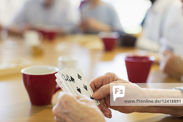 Close up senior woman playing cards with friends in community center