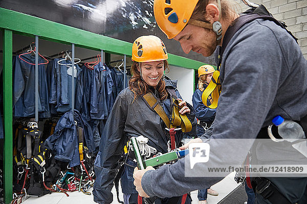 Man helping woman with zip line equipment