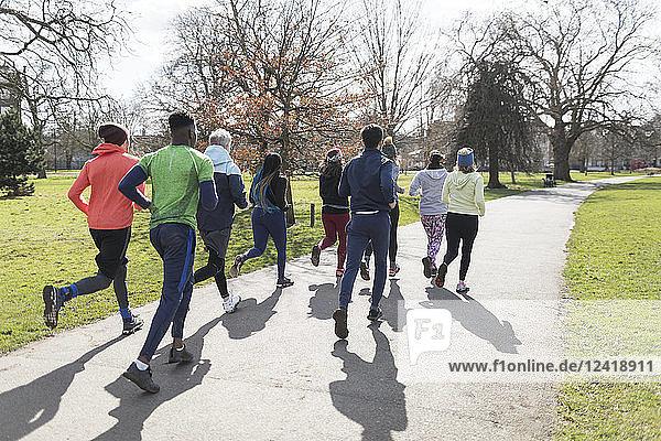Runners running in sunny park