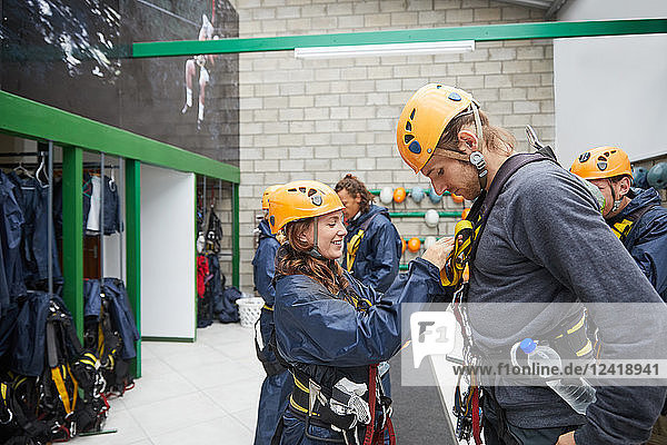 Woman helping man with zip line equipment