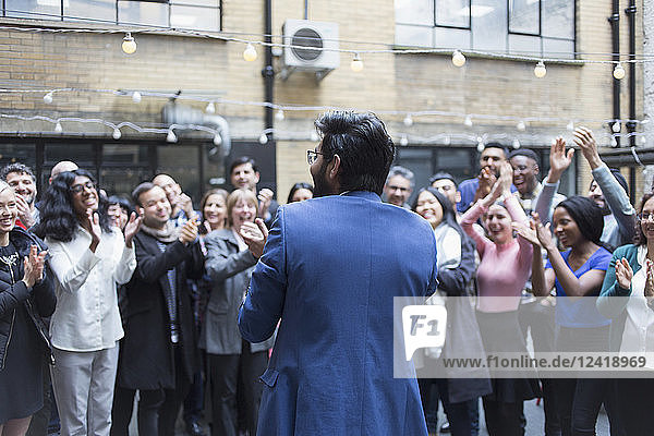 Business people cheering for businessman in courtyard