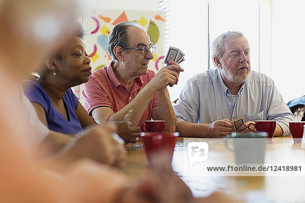 Senior friends playing cards at table in community center