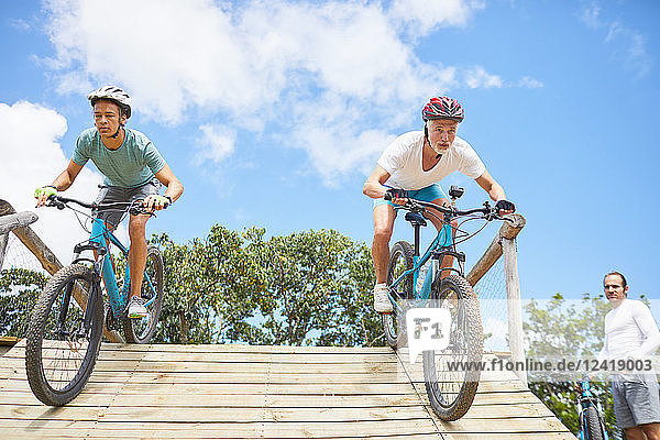 Focused men mountain biking on obstacle course ramp
