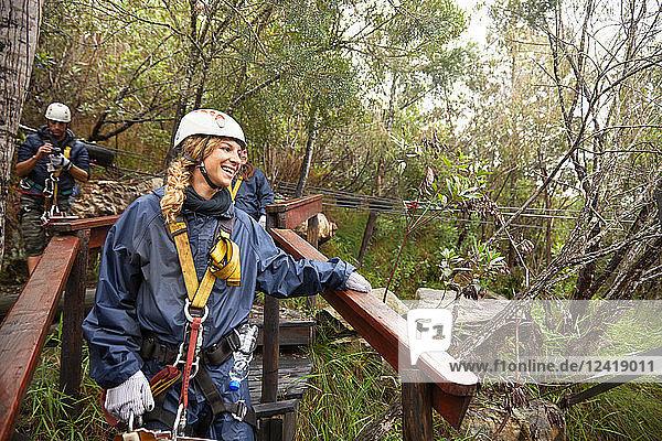 Smiling woman preparing to zip line in woods