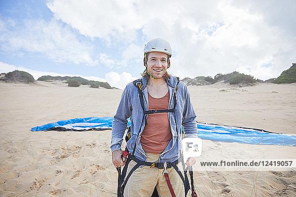 Portrait confident male paraglider on beach