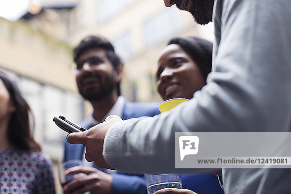 Man texting with smart phone at party