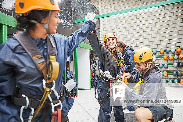 Women friends high-fiving  preparing zip line equipment