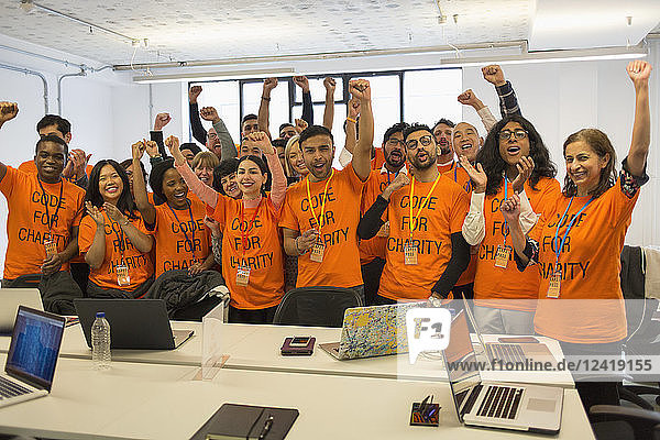Portrait confident hackers cheering  coding for charity at hackathon