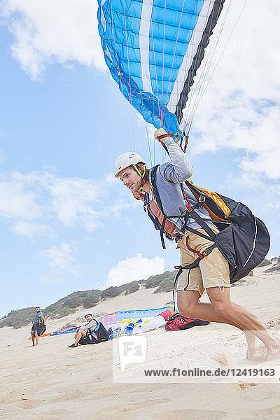 Male paraglider running on beach