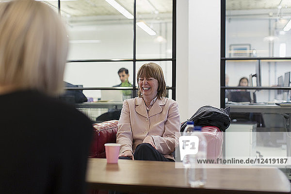 Laughing businesswoman in meeting