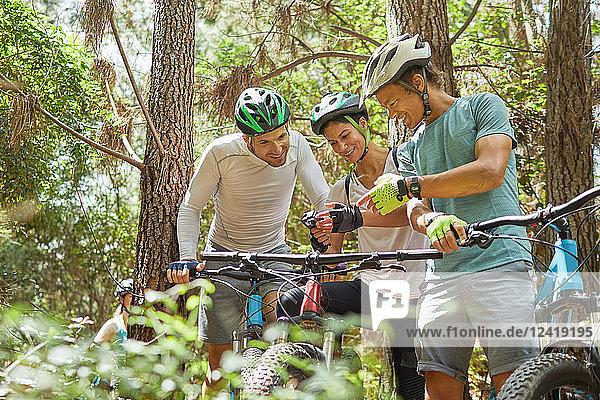 Friends mountain biking  using wearable camera in woods