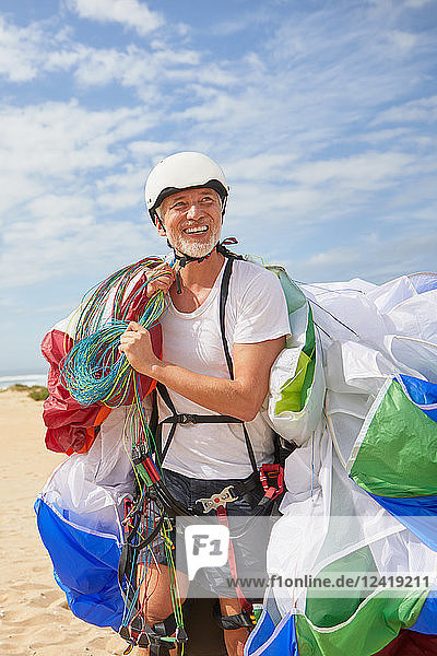 Smiling mature male paraglider carrying equipment and parachute