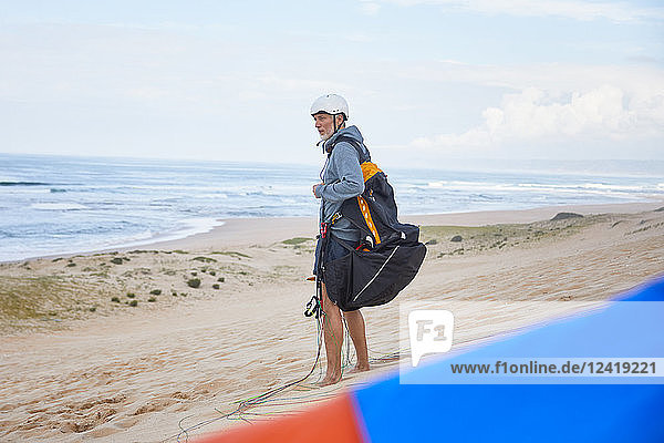 Paraglider with parachute backpack on ocean beach