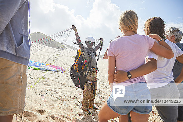 Students watching male paragliding instructor with equipment on sunny beach