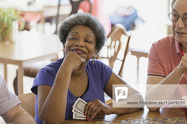 Confident  happy senior woman playing cards with friends in community center